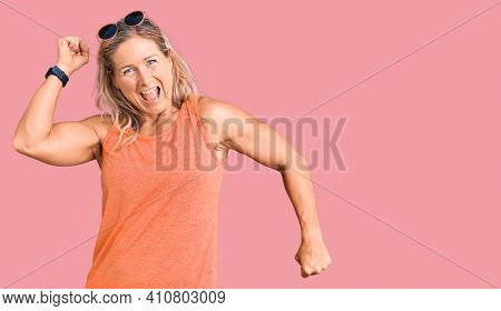 Middle age fit blonde woman wearing casual summer clothes and sunglasses dancing happy and cheerful, smiling moving casual and confident listening to music