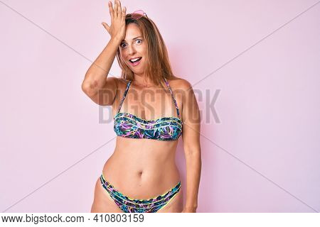 Middle age hispanic woman wearing bikini surprised with hand on head for mistake, remember error. forgot, bad memory concept.