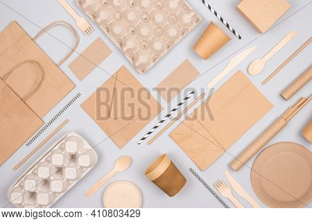 Flat Lay Composition With Eco-friendly Tableware And Kraft Paper Food Packaging On Gray Background.