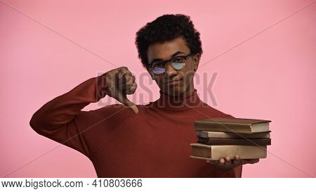 Displeased African American Teenage Boy In Glasses Holding Books While Showing Thumb Down Isolated O