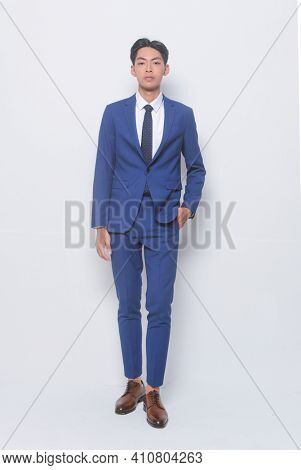 full length young handsome man wearing in blue suit ,tie with white shirt and blue pants , brown shoes standing hands holds pockets standing on white background,