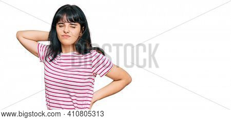 Young hispanic girl wearing casual clothes suffering of neck ache injury, touching neck with hand, muscular pain
