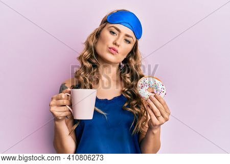 Young blonde girl wearing sleep mask and pyjama having breakfast looking at the camera blowing a kiss being lovely and sexy. love expression.