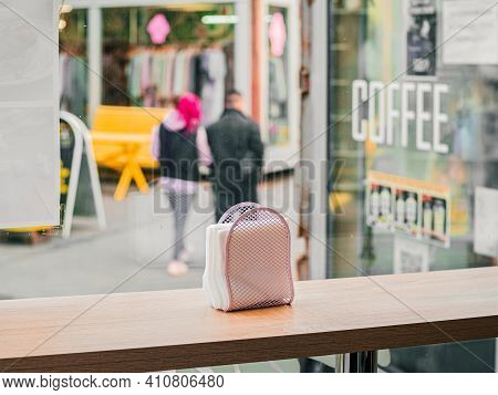 Pink Mesh Napkin Holder With White Paper Napkins Stands On A Wooden Table By The Window In A Cafe. B