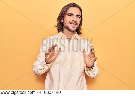 Young handsome man wearing business clothes disgusted expression, displeased and fearful doing disgust face because aversion reaction. with hands raised