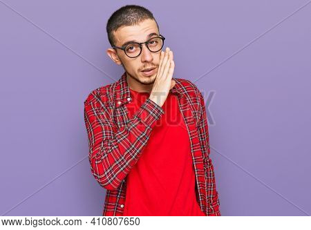 Hispanic young man wearing casual clothes hand on mouth telling secret rumor, whispering malicious talk conversation