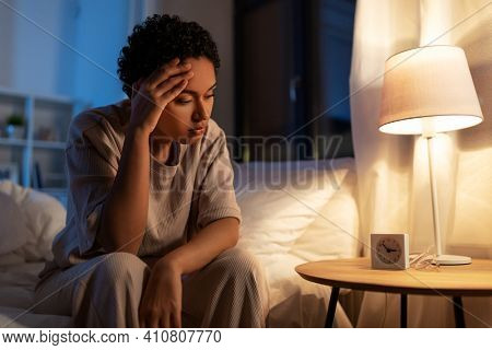 people, bedtime and rest concept - stressed african american woman having headache in bed at night