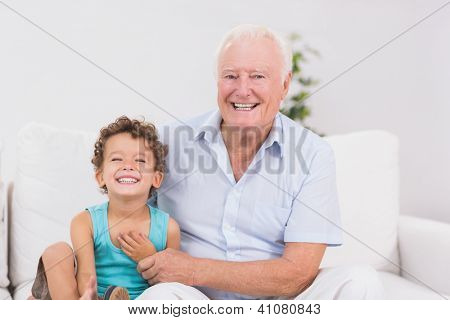 Cheerful grandfather and grandson sitting on the sofa while smiling