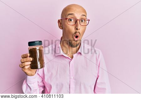 Bald man with beard holding soluble coffee scared and amazed with open mouth for surprise, disbelief face