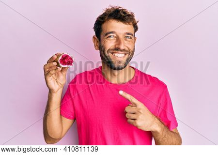 Handsome man with beard holding pink geode precious gemstone smiling happy pointing with hand and finger