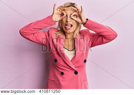 Middle age caucasian woman wearing business jacket doing ok gesture like binoculars sticking tongue out, eyes looking through fingers. crazy expression.