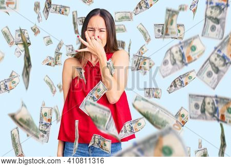 Beautiful brunette young woman wearing casual clothes smelling something stinky and disgusting, intolerable smell, holding breath with fingers on nose. bad smell