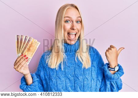 Young blonde girl holding 100 norwegian krone banknotes pointing thumb up to the side smiling happy with open mouth