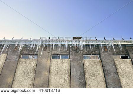 An Emergency Building With Dangerously Hanging Ice Icicles. Concrete Structure In Need Of Repair