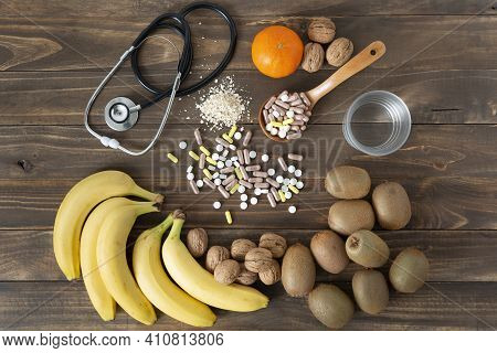 Some Nutrients, Fruits And Medicines To Take Care Of Food On A Dark Wood Background. Healthy Lifesty