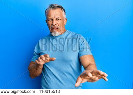 Middle age grey-haired man wearing casual clothes disgusted expression, displeased and fearful doing disgust face because aversion reaction. with hands raised