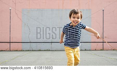 Smiling little running towards camera on basque pelota court, toddler holding twigs in his left hand.