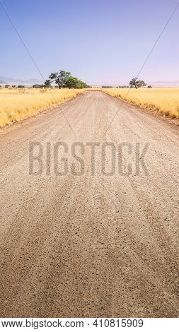 Desert Gravel Road With Vanishing Point Displaying The Way Forward. 9:16 Smartphone Format Or Vertic