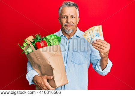 Middle age grey-haired man holding groceries and swiss franc banknotes relaxed with serious expression on face. simple and natural looking at the camera.
