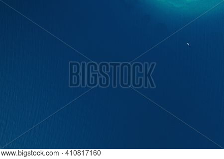 Blue Sea Water Surface. Aerial Top View. Small Waves And A Tiny Boat In The Sea. Splendid Surface Of