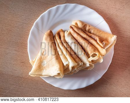 Freshly Baked Pancakes Rolled Up In Triangles Lie On A White Plate Top View Close-up