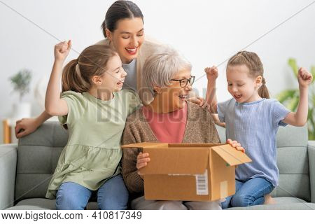 Grandmother, her daughter and granddaughters are unpacking cardboard box at home.