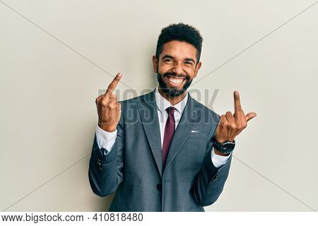 Handsome hispanic man with beard wearing business suit and tie showing middle finger doing fuck you bad expression, provocation and rude attitude. screaming excited