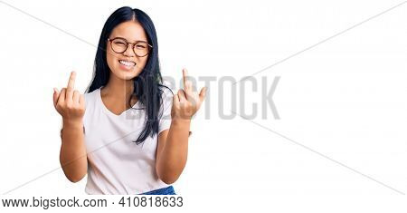 Young beautiful asian girl wearing casual clothes and glasses showing middle finger doing fuck you bad expression, provocation and rude attitude. screaming excited