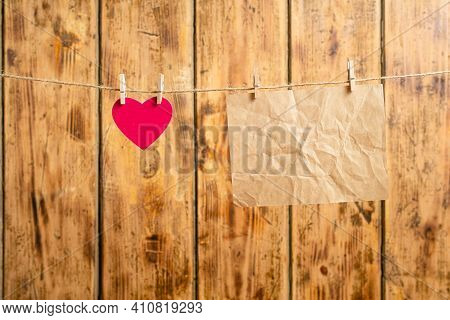 A Small Pink Heart Hangs From A Rope Next To An Old Parchment. In The Background There Is An Old Woo