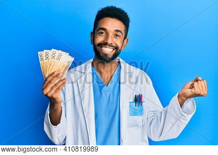 Handsome hispanic man with beard wearing medical uniform holding 500 norwegian krone screaming proud, celebrating victory and success very excited with raised arm