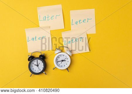 Alarm Clock With Sticky Notes Later, Tomorrow, Next Day And After On The Yellow Background. Procrast