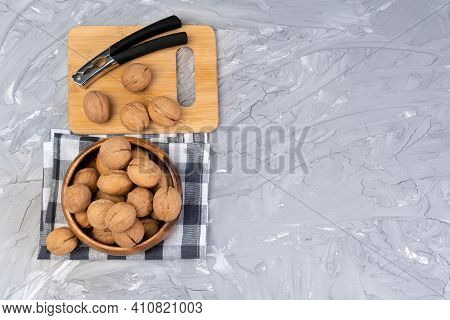 Cracks Walnuts With A Nutcracker. Whole Walnuts, Walnuts Kernels. Copy Space