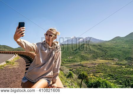 Young Woman Taking Selfie Or Vlogging On Mobile Phone During Her Travel On The Island. Lifestyle Tra