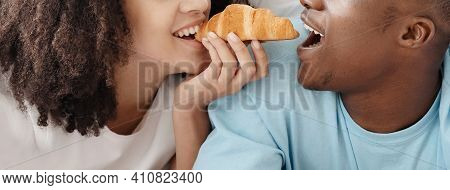 Happy Young Couple In Bed In Morning And Having Breakfast. Cheerful African American Man And Woman E
