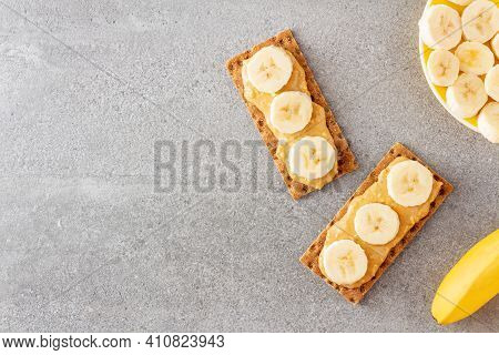 Whole Grain Crispbread And Peanut Butter With Banana Chunks On Stone Table. Healthy Snack Made Of Ry