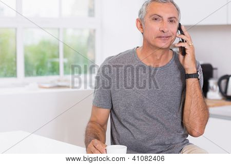 Man drinking while phoning in the kitchen