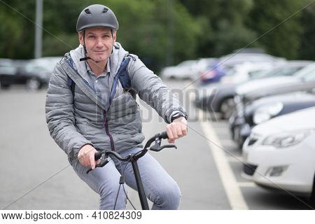 Mature Caucasian man in a bicycle helmet on his bike on a parking lot