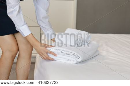 Room Service Putting Stack Of Fresh White Bath Towels On The Bed Sheet. Female Housekeeper Putting C