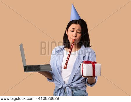Virtual Celebration During Quarantine. Sad Asian Woman Wearing Hat And Using Party Blower Celebratin