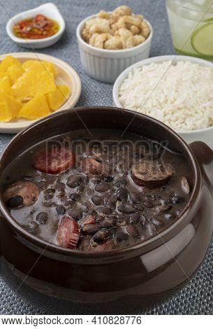 Traditional Brazilian Feijoada With Rice, Orange, Cracklings, Pepper And Caipirinha.