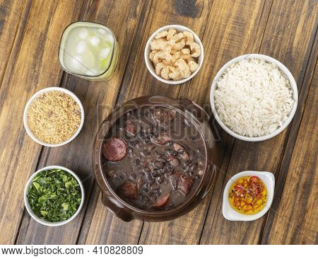 Traditional Brazilian Feijoada With Kale, Manioc Flour, Rice, Pepper, Cracklings And Caipirinha