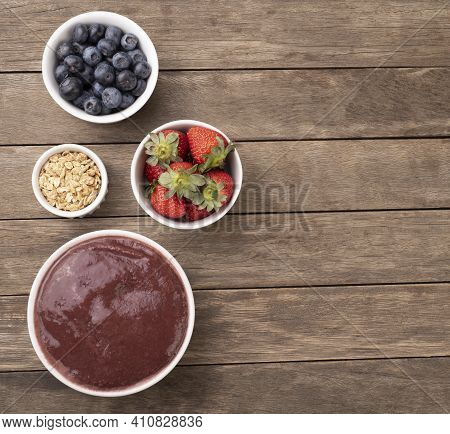 Brazilian Typical Acai Bowl With Fruits And Muesli Over Wooden Background With Copy Space.