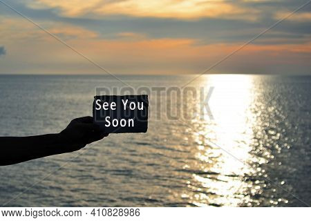 See You Soon Text On Hand Holding Torn Paper With Blurred Background Of Sunset At The Beach Of Tanju