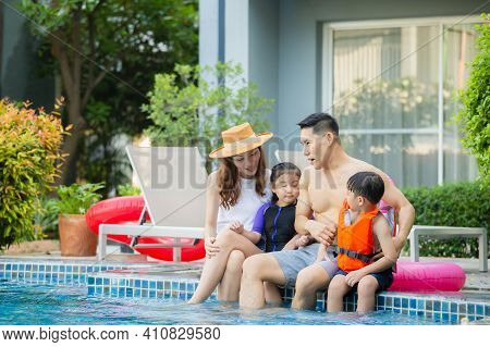 Young Asian Family Relaxing In Swimming Pool. Family On Vacation Having Fun By Pool, Happiness Lifes