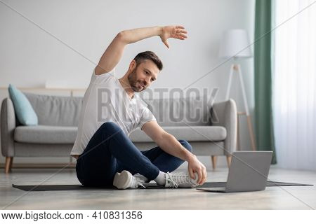 Positive Athletic Bearded Middle-aged Man Stretching At Home, Using Laptop, Watching Sport Videos On