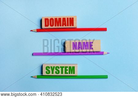 On A Blue Background, Three Colored Pencils, Three Wooden Blocks With Text Domain Name System