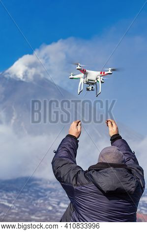 Male Launches Flying Drone Quadcopter Uav With Digital Camera On Background Of Volcano Eruption, Mou