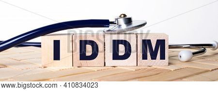 Wooden Cubes With The Word Iddm On A Wooden Background And A Stethoscope On Them. Medical Concept