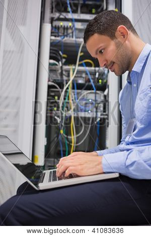 Man using laptop beside servers in data center