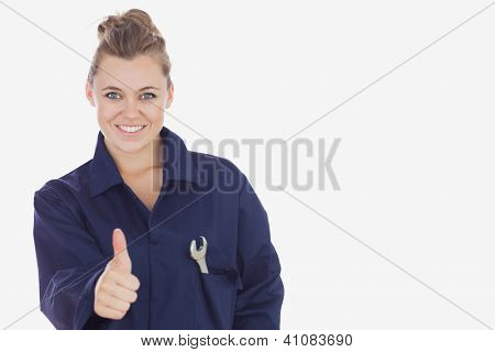 Portrait of female technician showing thumbs up sign over white background